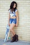 Mädchen, das auf Backsteinmauer mit Rochenbrett sich lehnt Stockfoto