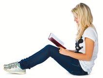 Mädchen, das auf das Fußboden- und Lesebuch legt Stockbilder