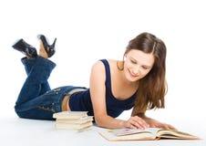 Mädchen, das auf das Fußboden- und Lesebuch legt Stockfotografie