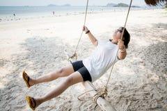 Mädchen, das auf dem Schwingen auf dem tropischen Strand, Paradiesinsel sitzt Lizenzfreies Stockfoto