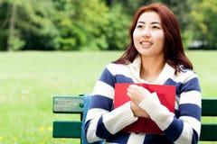 Mädchen, das auf der Bank, Buch halten sitzt Stockfoto