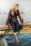Mädchen, das auf einem Pier sitzt Lizenzfreie Stockfotos