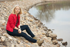 Mädchen, das auf einem Steinstrand nahe Wasser sitzt Lizenzfreie Stockbilder