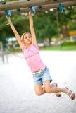 Mädchen, das auf Spielplatzschwingen baumelt Stockbild