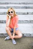 Mädchen, das auf Treppen unter Verwendung des Handys sitzt Stockbilder