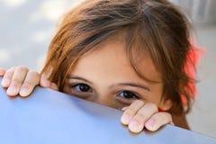 Mädchen, das über eine Tabelle mit glücklichen Augen späht Stockfotos