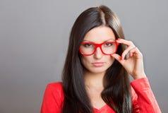 Mädchen, das über Gläsern schaut Lizenzfreie Stockbilder