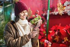 Mädchen, das Blumenzusammensetzungen am Weihnachtsmarkt kauft Stockbild
