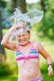 Mädchen, das den Spaß im Freien mit Wasser hat Stockfoto