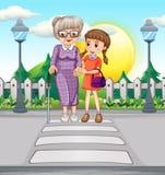Mädchen, das der alten Frau kreuzt die Straße hilft Stockbild