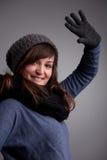 Mädchen, das an der Kamera mit warmem Hutschal und -handschuhen wellenartig bewegt Lizenzfreies Stockbild