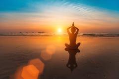 Mädchen, das in der Yogahaltung auf dem Strand durch das Meer bei Sonnenuntergang sitzt relax Lizenzfreie Stockfotos