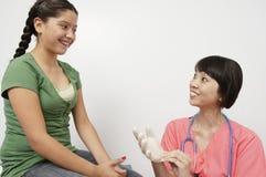 Mädchen, das Doktor Wearing Hand Glove betrachtet Lizenzfreies Stockbild
