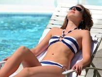Mädchen, das durch das Pool ein Sonnenbad nimmt Stockfotografie