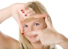 Mädchen, das durch ein Feld gebildet durch ihre Finger schaut Stockfotos