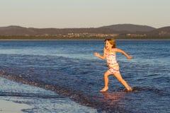 Mädchen, das durch Ozean läuft Stockfoto