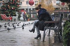 Mädchen, das durchdacht auf der Bank sitzt Stockfotografie