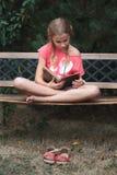 Mädchen, das ein Buch auf einer Bank im Park liest Stockfotos