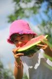 Mädchen, das eine neue Wassermelonescheibe isst Stockfotos