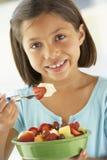 Mädchen, das eine Schüssel frischen Fruchtsalat isst Stockfotografie