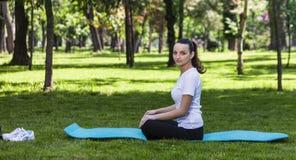 Mädchen, das in einem grünen Park sich entspannt Stockfoto