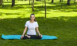 Mädchen, das in einem grünen Park sich entspannt Lizenzfreie Stockbilder