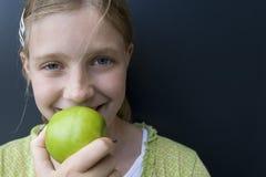 Mädchen, das einen grünen Apfel isst Lizenzfreie Stockfotos