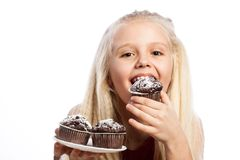 Mädchen, das einen Schokoladenkuchen beißt Stockfotos