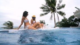 Mädchen, das in einen Swimmingpool schwimmt spritzen Sie herum im Swimmingpool, mit einem sexy Mädchen in einem HotelSwimmingpool stock video