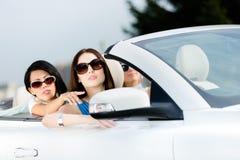 Mädchen, das etwas aus dem konvertierbaren Auto heraus zeigt Stockfotos