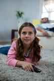 Mädchen, das fernsieht, auf der Wolldecke im Wohnzimmer zu liegen Stockfoto