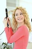 Mädchen, das Frisur mit flachem Eisen tut Stockfoto