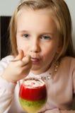 Mädchen, das Fruchtkremeis von einem Glas isst Stockfotos