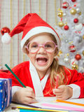Mädchen, das glücklich zeichnender Gutschein als Geschenk für Weihnachten lächelt Lizenzfreies Stockbild