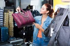 Mädchen, das Handtasche im Speicher wählt Stockfotos