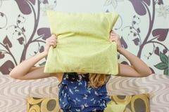 Mädchen, das hinter einem Kissen sich versteckt Lizenzfreie Stockfotografie