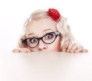 Mädchen, das hinter einem Schreibtisch sich versteckt Stockbild