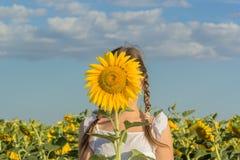 Mädchen, das hinter gelber Blumensonnenblume sich versteckt Stockfotografie