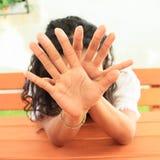 Mädchen, das hinter Händen sich versteckt Stockfotografie