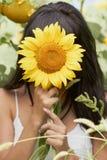 Mädchen, das hinter Sonnenblume sich versteckt Stockfoto