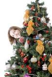 Mädchen, das hinter Weihnachtsbaum sich versteckt Stockfotos