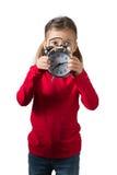 Mädchen, das ihr Gesicht hinter Borduhr versteckt Stockbild