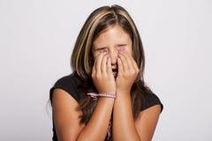 Mädchen, das ihre Augen mit ihren Händen abdeckt Stockfotografie