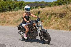 Mädchen, das italienisches Motorrad Ducati reitet Stockfotografie