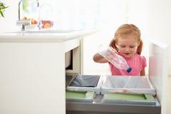 Mädchen, das Küchen-Abfall im Behälter aufbereitet Stockbilder