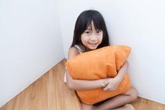 Mädchen, das Kissenorange umarmend sitzt Stockfotos