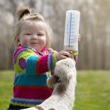 Mädchen, das Lamm mit der Flasche füttert Stockfotos