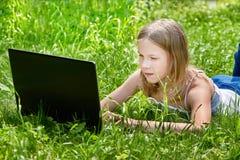Mädchen, das Laptop auf Gras verwendet Lizenzfreie Stockfotografie