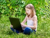 Mädchen, das Laptop auf Gras verwendet Stockfotografie