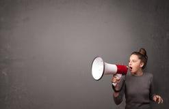 Mädchen, das in Megaphon auf Kopienraumhintergrund schreit Lizenzfreie Stockfotos